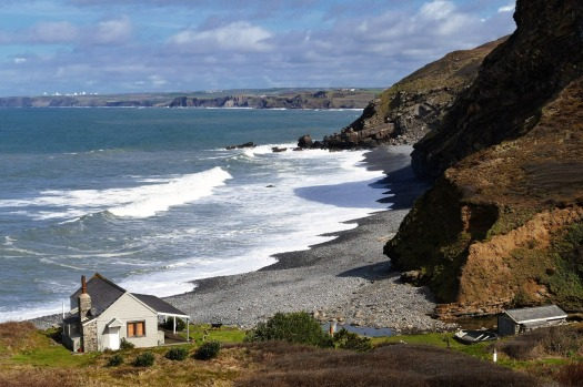 A British coastline with a small white cottage in the foreground and cliffs nearby